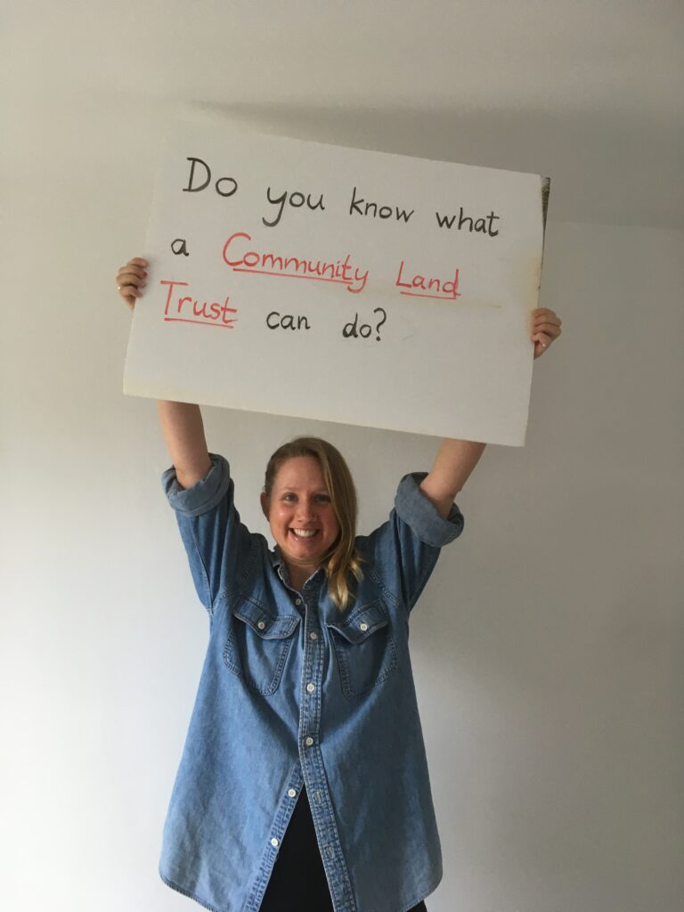 """Lady holding a sign saying """"Do you know what a community land trust can do?"""""""