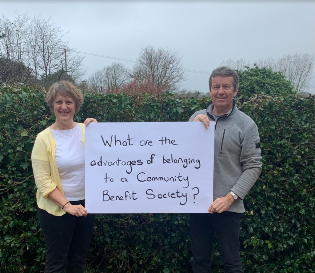 """2 people holding a sign saying """"What are the advantages of belonging to a community benefit society?"""""""